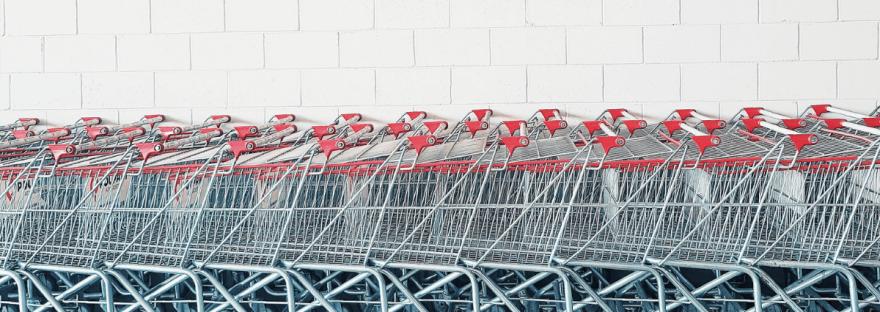 A photo by Gabrielle Ribeiro of a line of shopping carts against a white brick wall.