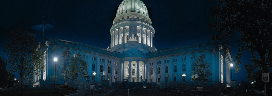 A panoramic image of the Capitol building at night.