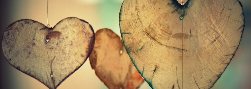 A photo by Ben Kerckx of three wooden heart ornaments hanging in a row.
