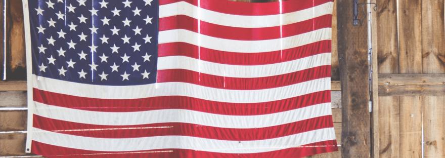 An American flag hangs on a wall inside a barn.
