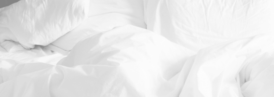 A black and white photo of an unmade bed with white pillows and sheets crumpled up.