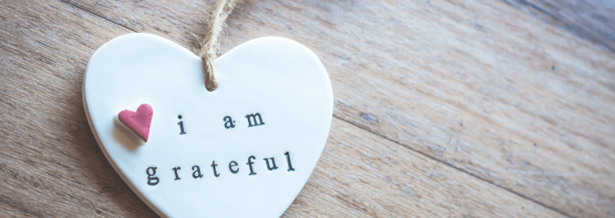 """A white heart-shaped ornament sits on a wooden table. Written on the heart is, """"I am grateful""""."""