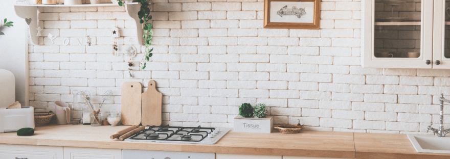 A beautifully clean kitchen with wooden counter tops and white brick walls.