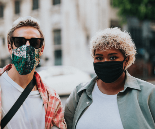 Two people standing outside wearing face masks to stop the spread of Covid-19. Photo by Nathan Dumlao.