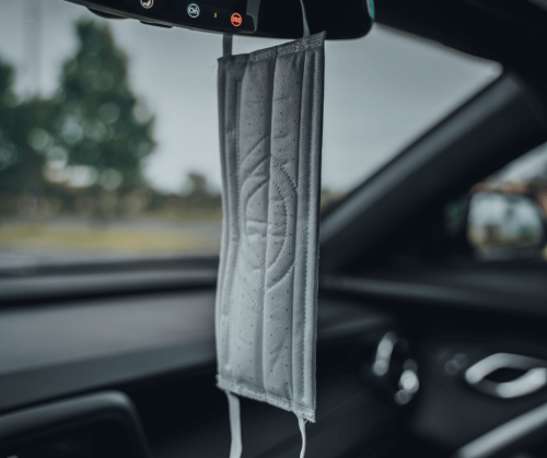 A face mask used to stop the spread of Covid-19 hangs from the rear view mirror in a car. Photo by Talia.