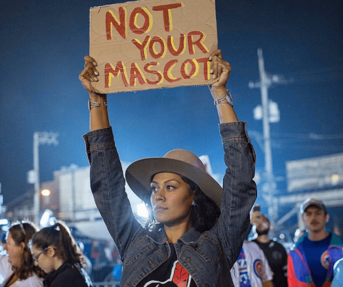 A photo by Tomás Karmelo Amaya of Siera Begaye holding up a protest sign that reads: Not Your Mascot.