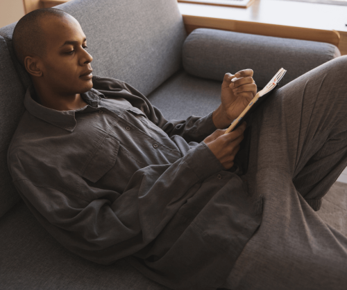A Black man sits reclining on a sofa with one leg up. On his thign he rests and write in a notebook.