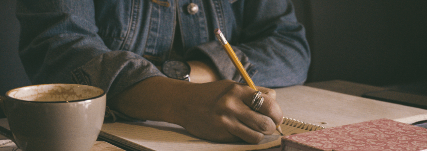 A Black woman sits at a table surrounded by notebooks and a cup of coffee. She is writing in one of the notebooks.