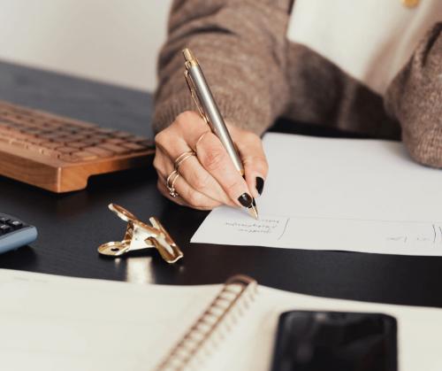 photo of a person writing on a sheet of white paper at a desk by karolina grabowska