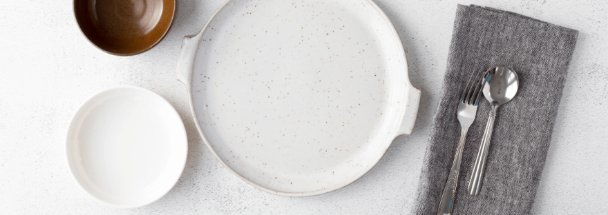 On a white table is a white dinner plate, grey napkin with spoon and fork on it, a small white plate and a small brown bowl.