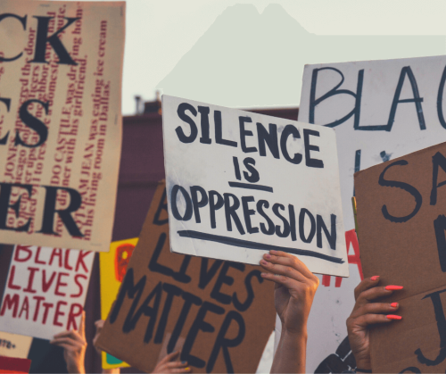 photo by kalea morgan showing a protester holding a sign that reads,'silence is oppression'
