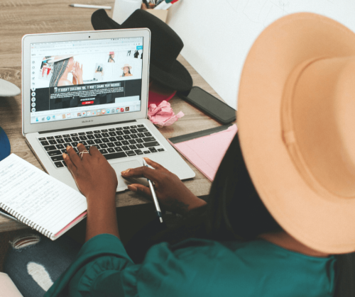 A woman wearing a hat sits at her desk and work on her laptop creating a blog post.