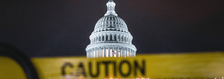 image by Andy Feliciotti showing the Capitol Building in D.C. at night with a yellow tape with the word 'caution' written on it in black lettering on a metal barrier in front of the building