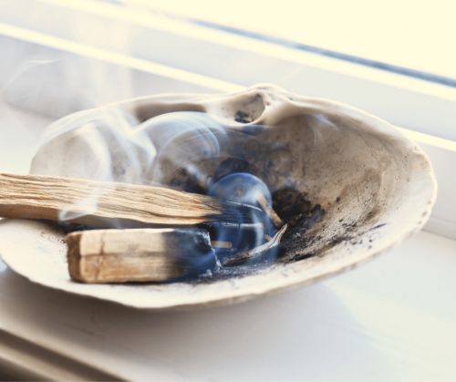 A burning palo santo smudge stick rests in an abalone shell.