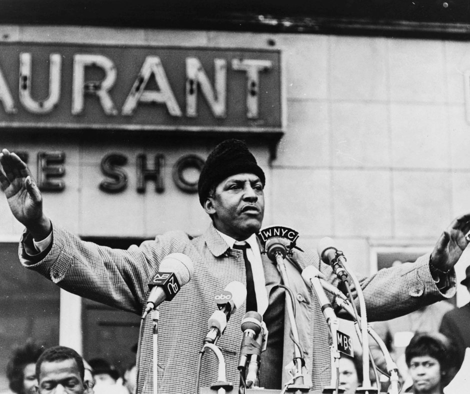 A black & white photo of Bayard Rustin giving a speech surrounded with microphones.