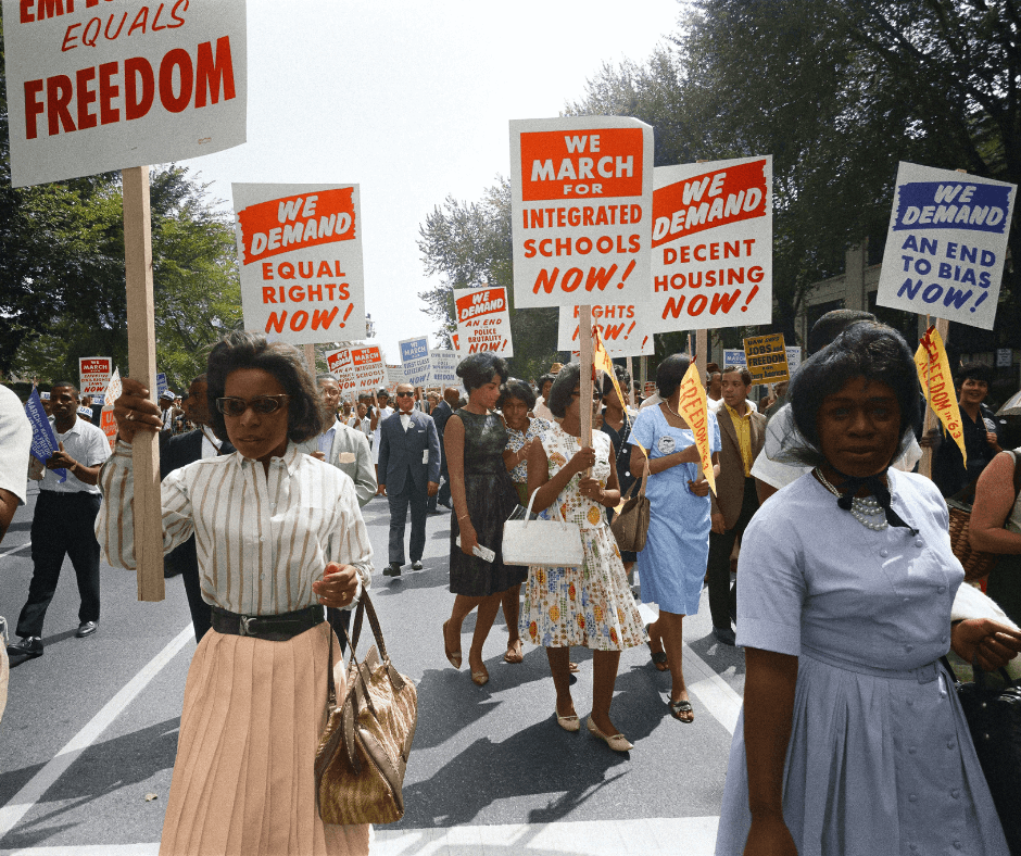 A photo of a 1963 Civil Rights march in Washington D.C of a procession of African Americans carrying signs for equal rights, integrated schools, decent housing, and an end to bias.