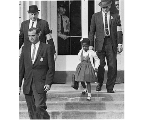 A black & white photo from 1960 of Ruby Bridges being escorted to school flanked by U.S. Marshals to protect her on her way to class.