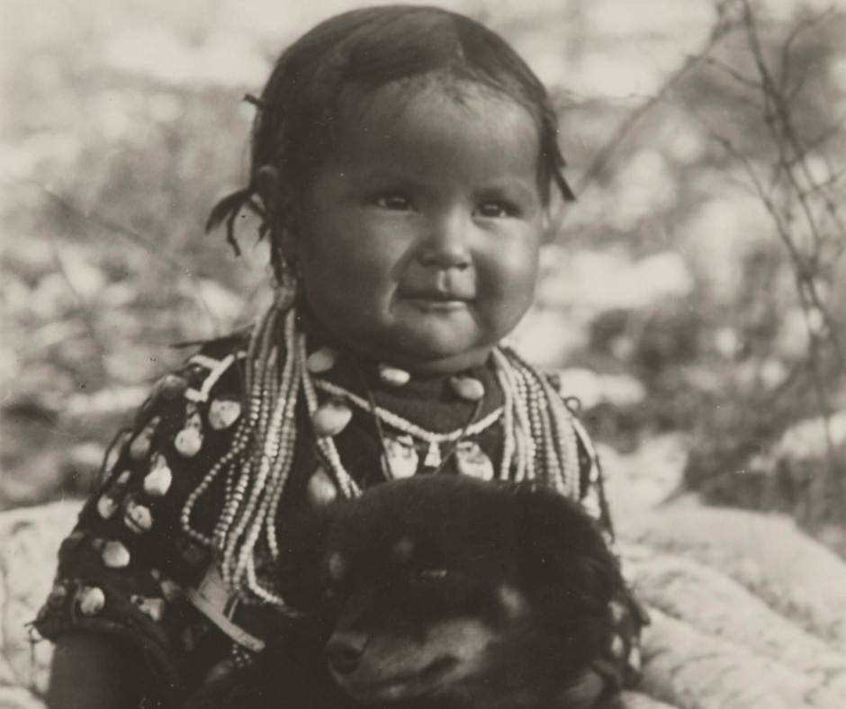 A sepia photograph taken in about 1910 of an unknown Native American child (possibly aged about 1-2 years) wearing shelled and beaded traditional dress and holding a puppy.