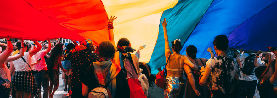 A group of people taking part in a Pride Parade walk under an extremely large rainbow Pride flag that they're holding above their heads.