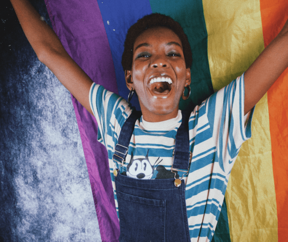 A photo by Jakayla Toney shows a happy, smiling Black person wearing thick, hooped silver earring, a blue and white striped t-shirt and dark blue denim overalls. They have their arms raised in celebration, holding the rainbow Pride flag.