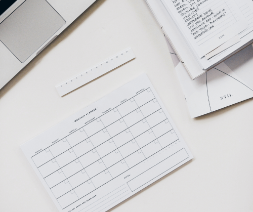 On a white desk sits an A4 paper monthly planner (left blank), a notebook open at a to-do list and an open laptop.