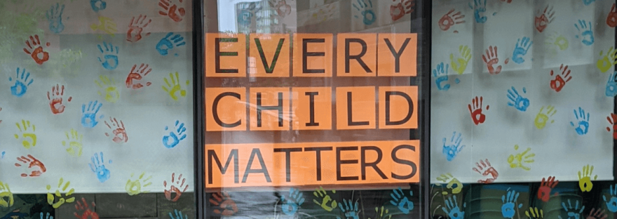 A photo taken by Community Archives shows a window display at Belleville Public Library with 'Every Child Matters' written on orange paper surrounded by blue, yellow and red handprints. The display is in recognition and solidarity with First Nations People after the discovery of indigenous children's mass graves found at Kamloops Residential School.