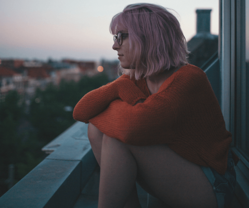 A young woman with pink hair, black glasses and wearing an orange sweater sits with her arms crossed over her raised knees. She's gazing out over a cityscape at dusk. Photo by Finn Hackshaw.