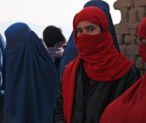 A photo by Canva user ArmyAmber of a group of Afghan women wearing blue burqas which covers the entire body and face and some teenage girls wearing red niqabs which cover the face showing only their eyes.