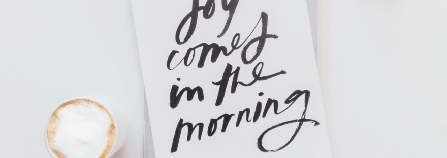 On a white table is a white sheet of paper with the words, 'Joy comes in the morning' written in a bold, black paintbrush style font. Next to it is a cappuccino and a pair of glasses. Photo by Sincerely Media on Unsplash.