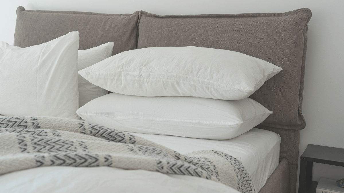 Four white pillows with a white and blue/grey woolen blanket rest on a recently made bed that has a brown material headboard and base. Photo via Casterly StockCanva.