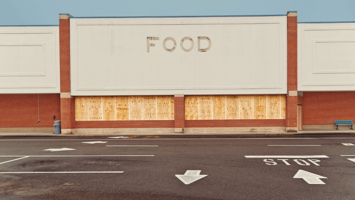 A photo of a boarded up out of business grocery store at dusk taken by Wendell and Carolyn via Canva.