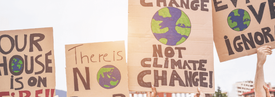 A photo via Canva/DisobeyArt shows the protest signs from a climate action march.