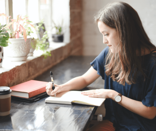 A woman with long brown hair sits at a rectangular, black table next to a window. She is writing in an affirmation journal. Photo by Hannah Olinger on Unsplash.
