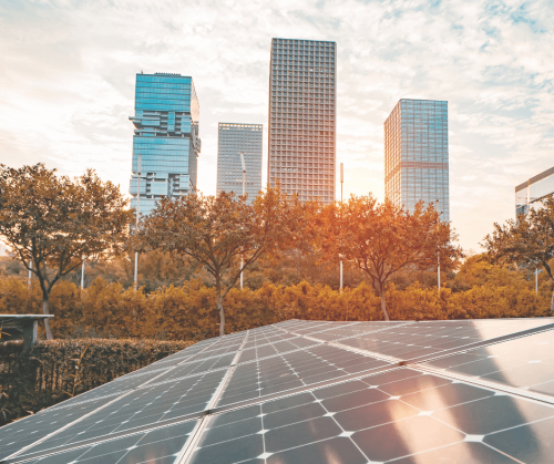 A photo via Canva/kynny of some solar panels in an urban city setting with some high rise buildings in the background.