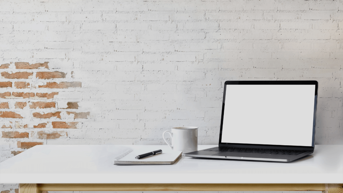 On a white table sits an open (blank) laptop with a notebook, pen and white coffee mug next to it. Behind it is a white brick wall. Photo by Bongkarn Thanyakij via Canva.
