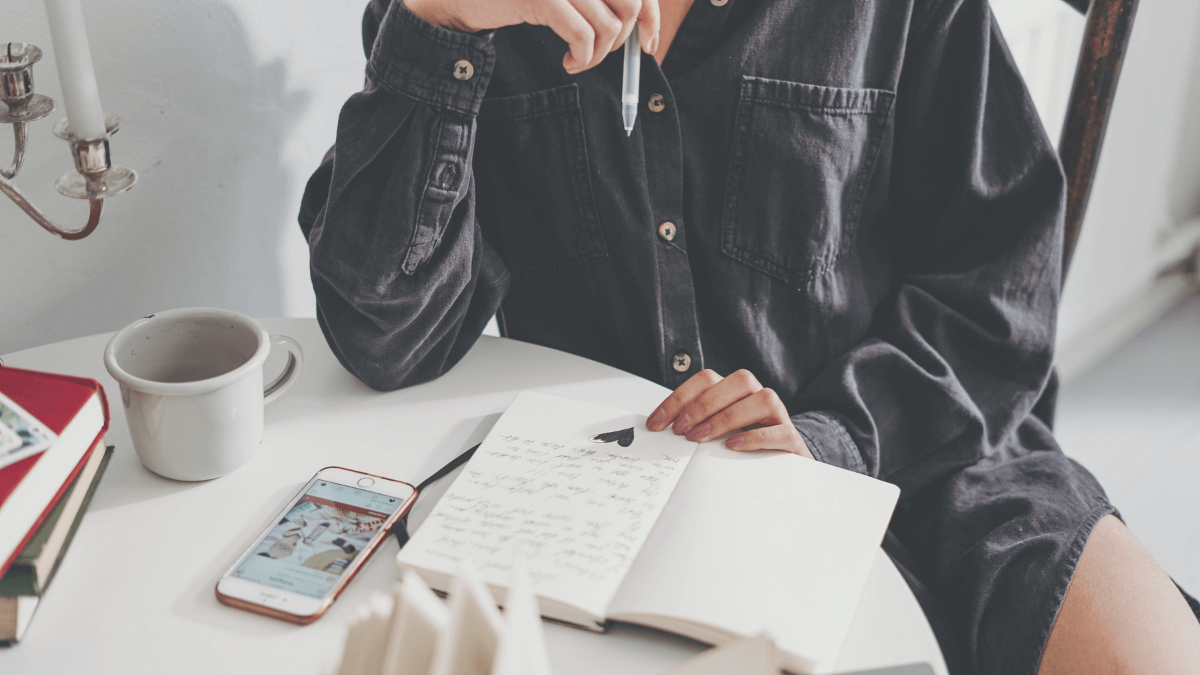 A person sits at a white table with an open journal. Their hand, holding a pen, is held under their chin as if they are thinking about what else to write. They have been inspired by quotes about creating a thriving mindset. Their phone and cup of coffee is nearby. Photo by cottonbro via Canva.